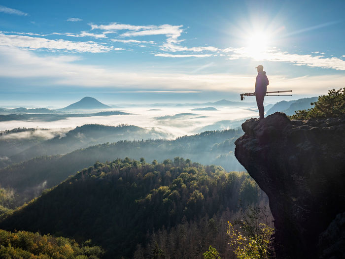 Photographer take picture with camera in morning hills. nature artist with photo equipment on rock
