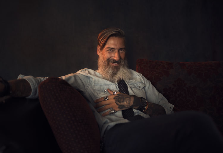 Portrait Of Smiling Hipster Man Sitting On Sofa