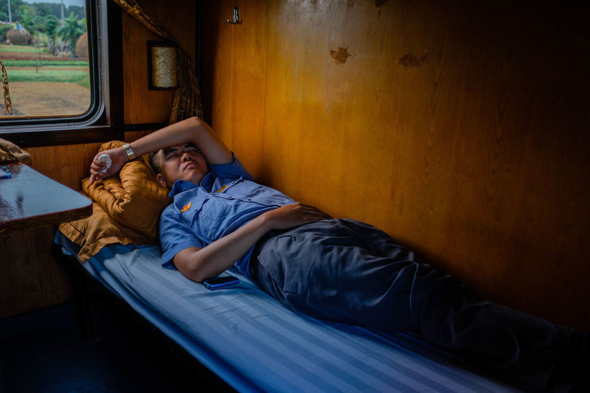 On board of the Reunification Express. Man At Work Take A Nap Uniform Vietnam Bed Conductor Emotion Furniture Indoors  Leisure Activity Lifestyles Lying Down Males  Men Real People Relaxation Resting Sitting Sleeping Togetherness Wood - Material The Week On EyeEm Editor's Picks
