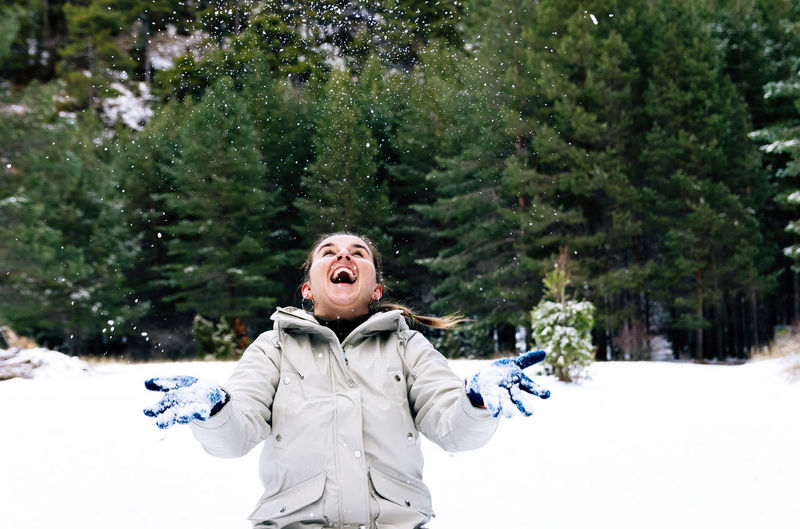 Smiling woman throwing snow mid air during winter