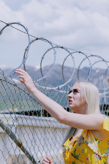 Barbed Wire Freedom Barrier Beautiful Woman Clothing Day Escape Fence Hairstyle Holding Human Arm Looking One Person Outdoors Prison Razor Wire Real People Sky Women Young Adult Young Women