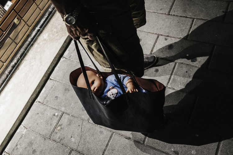 Low section of man holding bag with doll while standing on footpath