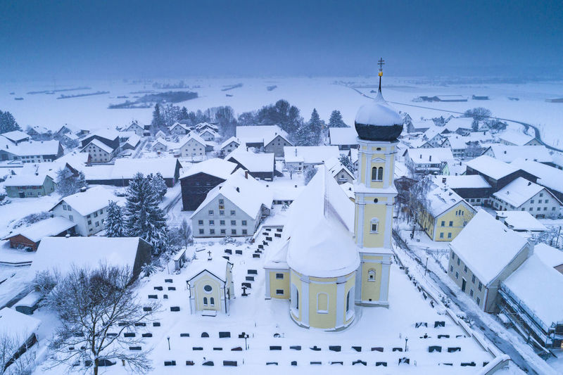 High angle view of snow covered houses and buildings against sky