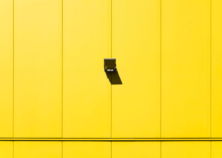 Low angle view of security camera of yellow wall