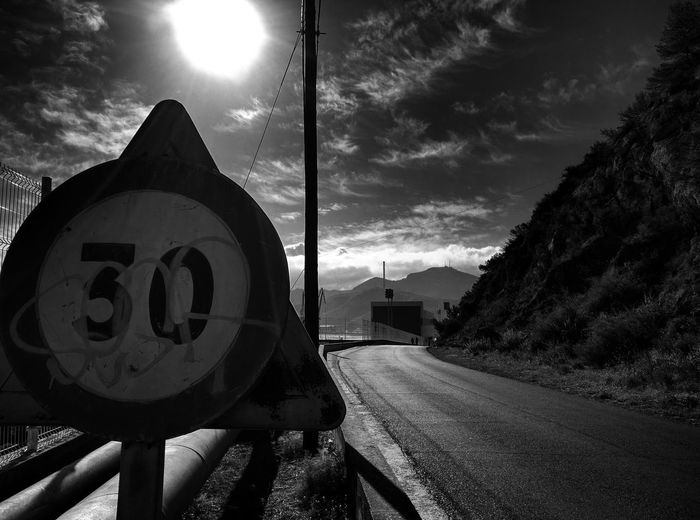Speed limit sign by road against sky