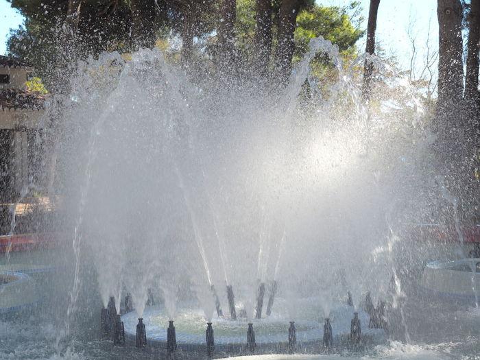 Group of people splashing water fountain