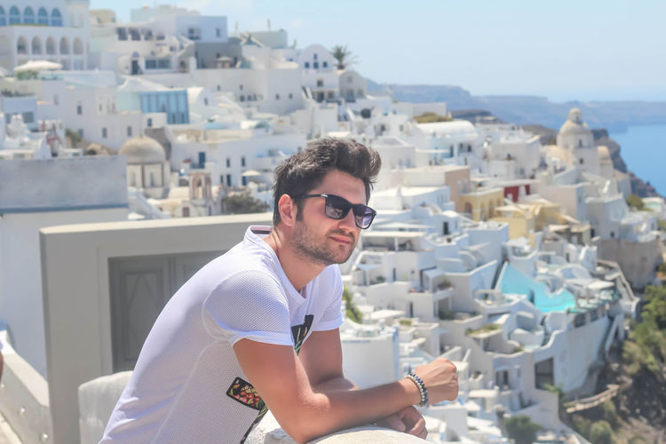 Man wearing sunglasses against townscape and sea