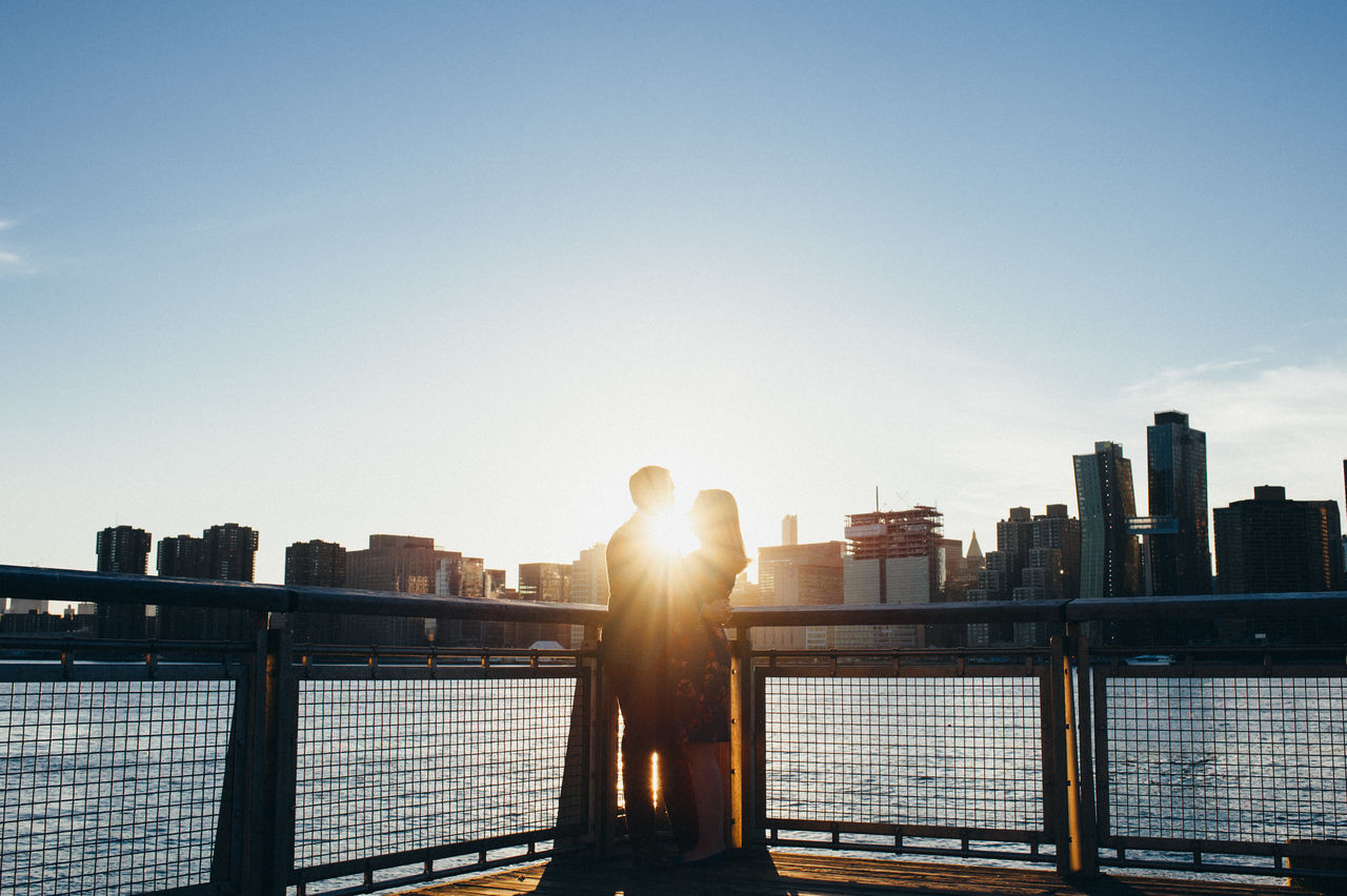 Couple in front of cityscape against sky during sunset