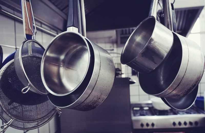 Close-up of colanders with saucepans in kitchen