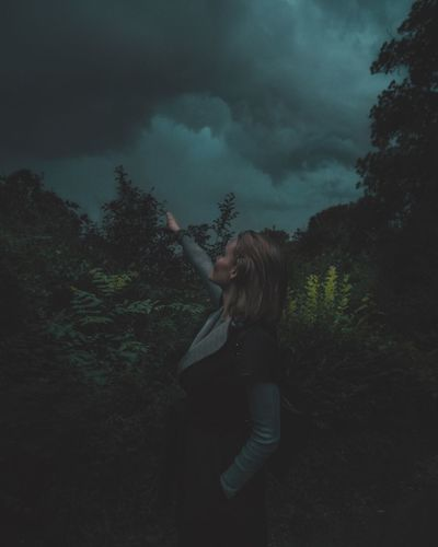 Young woman with hand raised standing amidst trees in forest against cloudy sky at dusk