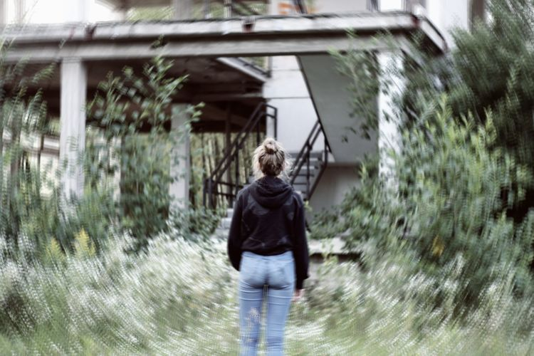 Rear view of young woman walking in water
