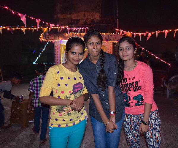 Arts Culture And Entertainment Bonding Celebration Enjoyment Friendship Girls Happiness Illuminated Leisure Activity Lifestyles Looking At Camera Night Outdoors People Portrait Real People Smiling Standing Togetherness Young Adult Young Women