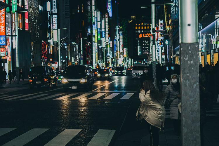 Illuminated city street by modern buildings at night