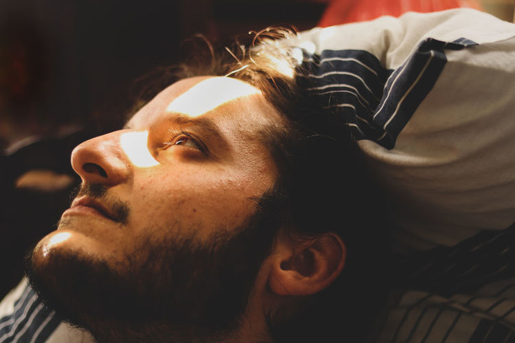 Close-up of thoughtful young man looking away while lying on bed