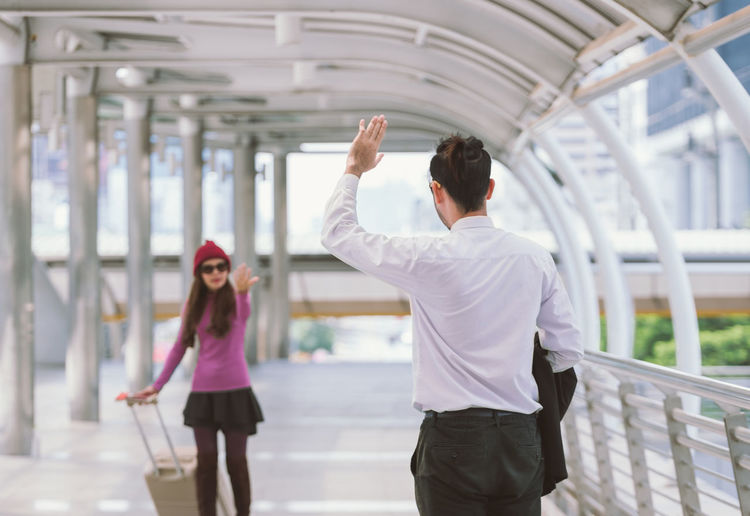 Couple Gesturing On Elevated Walkway At Airport