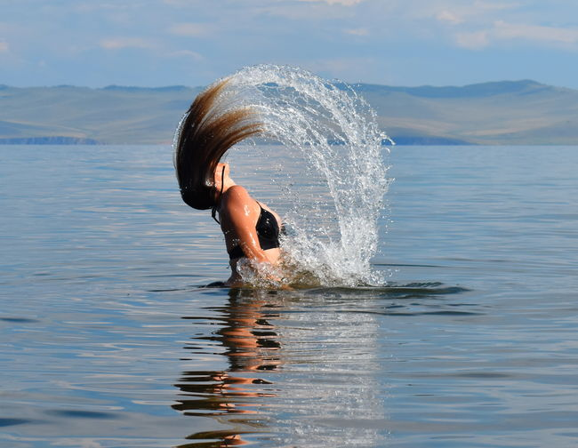 Woman with long hair swimming in sea
