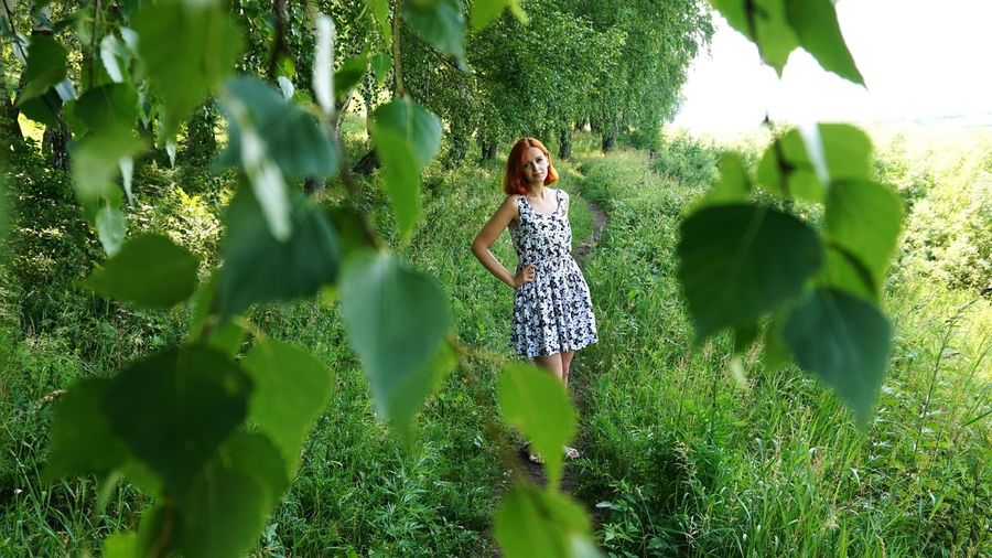 Portrait of young woman standing amidst plants on field