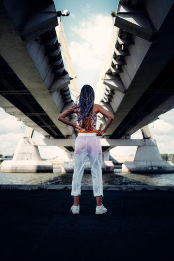 Rear view of people standing on bridge in city