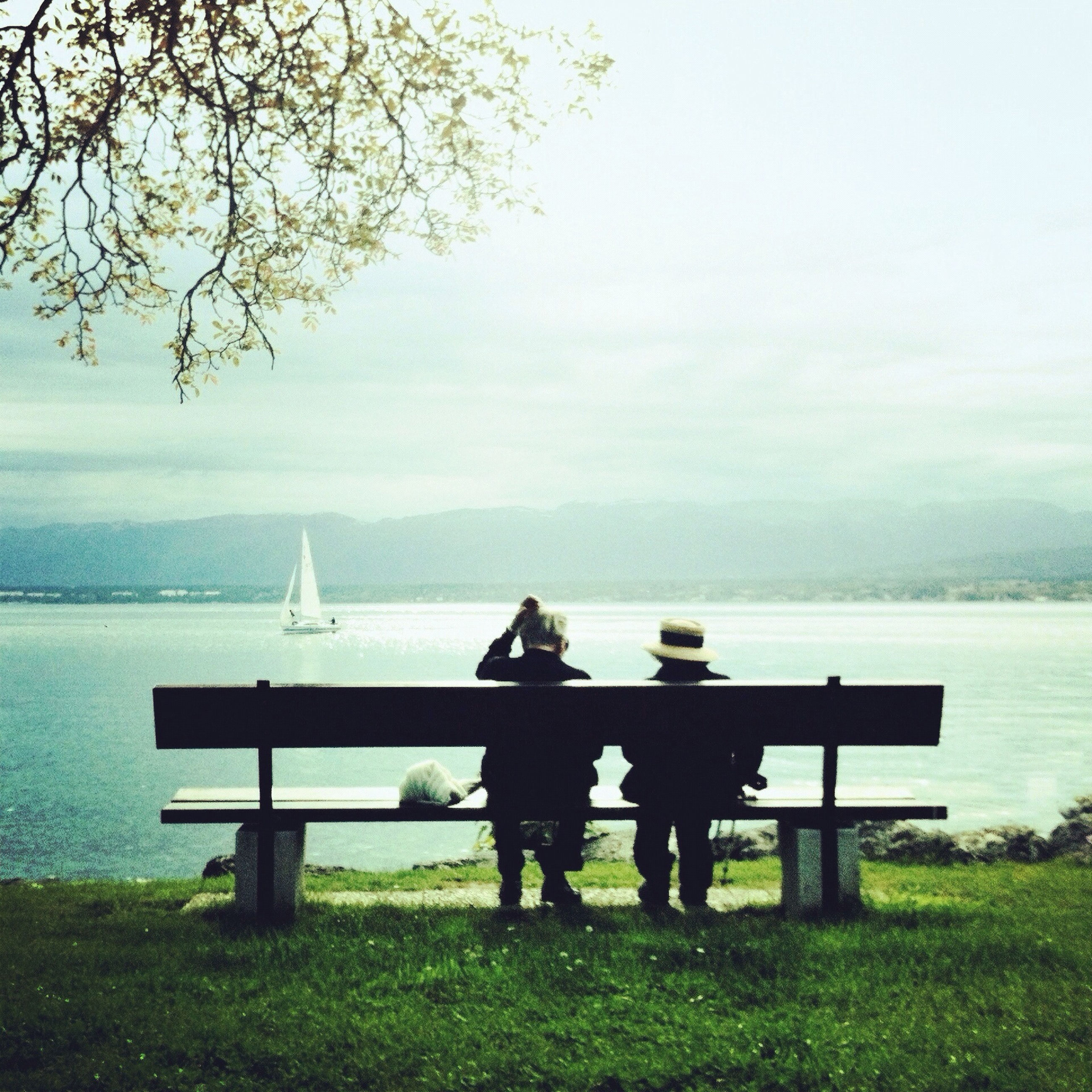water, lifestyles, rear view, leisure activity, men, togetherness, bench, person, full length, tranquility, tranquil scene, sea, sitting, sky, nature, lake, standing, relaxation