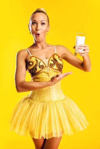 Portrait of surprised beautiful ballerina holding milk glass against yellow background