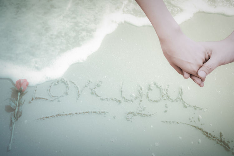 Cropped image of couple with holding hands over text on sand
