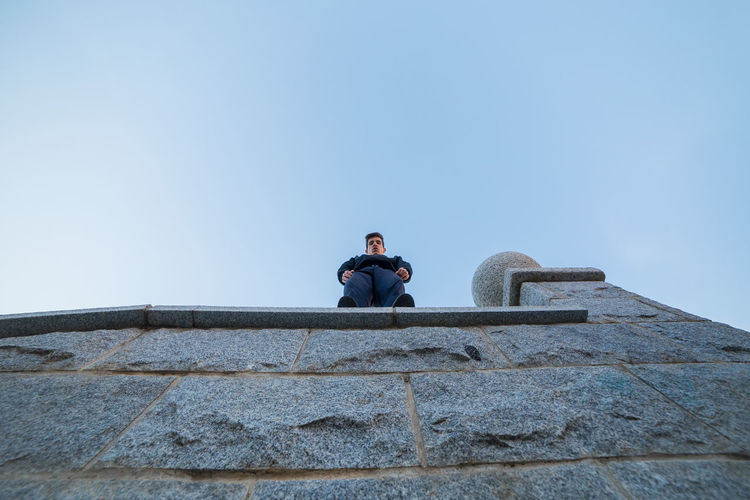Full Length Portrait Of Man Standing On Wall Against Clear Sky