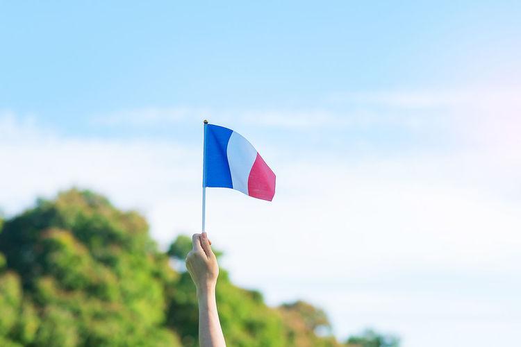 Hand holding flag against sky
