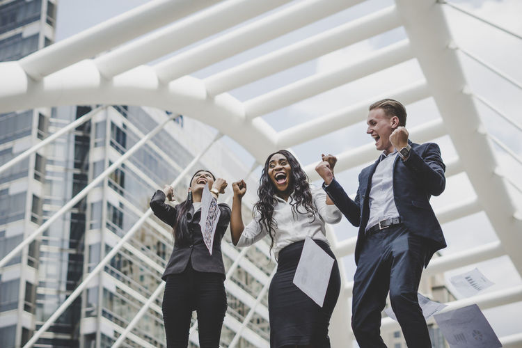 Cheerful Business People Jumping With Clenched Fists Against Metallic Structure