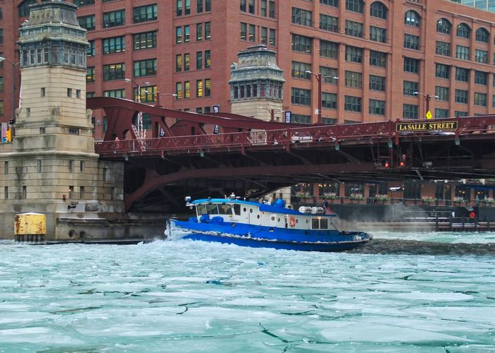 Boat speeding through a frozen river to break up chunks of ice in Chicago downtown loop. Chicago Chicago River Chicago Riverwalk Downtown Chicago Frozen Ice January Morning Winter Architecture Boat Bridge - Man Made Structure Bridgehouse Building Exterior Built Structure City Cracked Ice Drawbridge  Droplets Frozen River Ice Chunks Outdoors Water Waves Windows Shades Of Winter Stories From The City