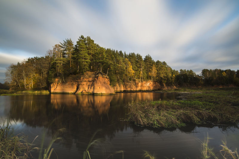 red sandstone cliff in sunlight Autumn Cliff Clouds Fall Landscape Reflection River Sandstone Sky Tree