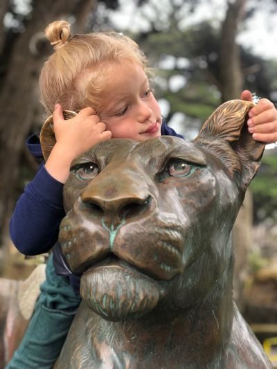 Close-up of girl sitting on lioness statue against trees