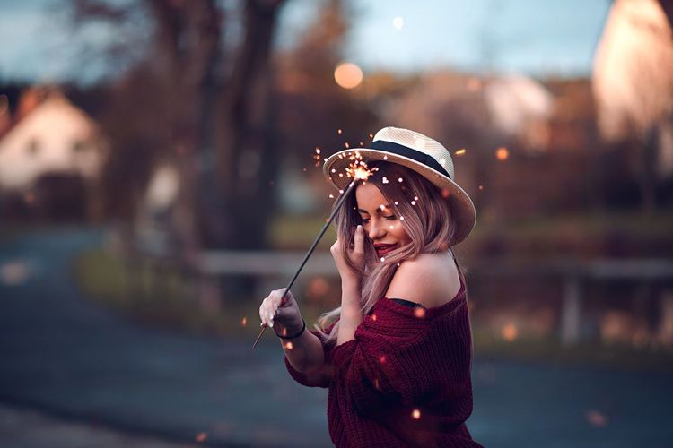 Young woman holding sparkler