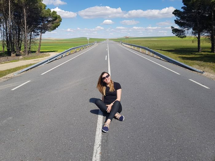 Portrait Of Woman Sitting On Road