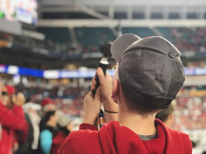 Rear view of boy wearing cap at stadium