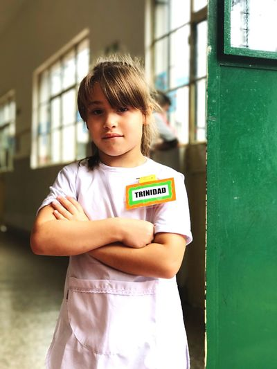 Portrait Of Girl Wearing Name Tag Standing With Arms Crossed In School