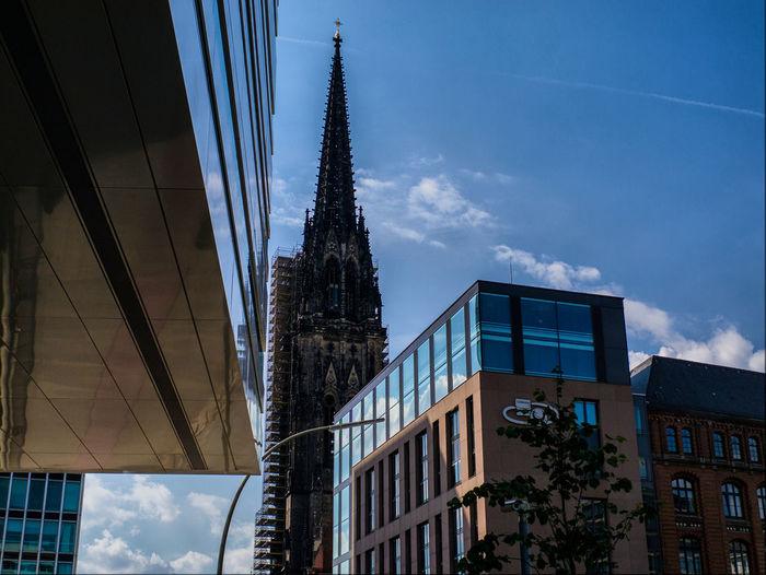 Buildings and church against sky