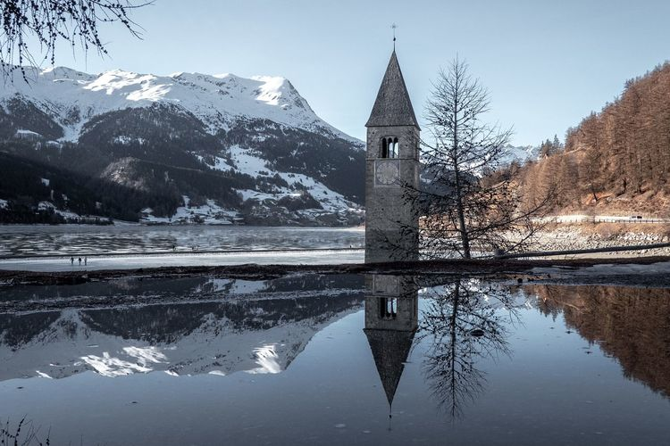 Reflection of building on snow covered mountain against sky