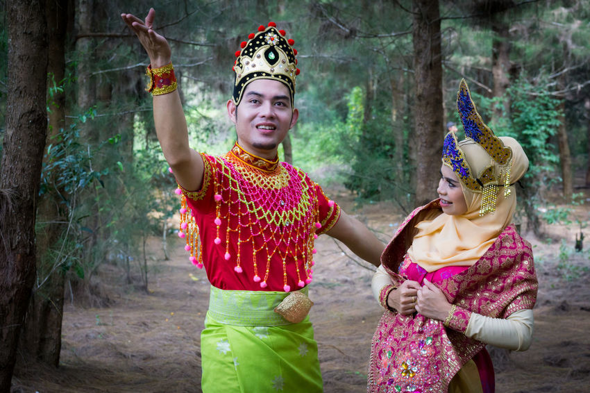 Specific to the villages of Kelantan, where the tradition originated, Mak Yong is performed mainly as entertainment or ritual purposes by couple of dancers. Adult Adults Only Beautiful Woman Crown Day Happiness Headdress Headwear Lifestyles Mak Yong Outdoors People Portrait Real People Smiling Traditional Clothing Two People Young Adult Young Women
