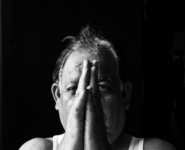 Portrait of man making face against black background