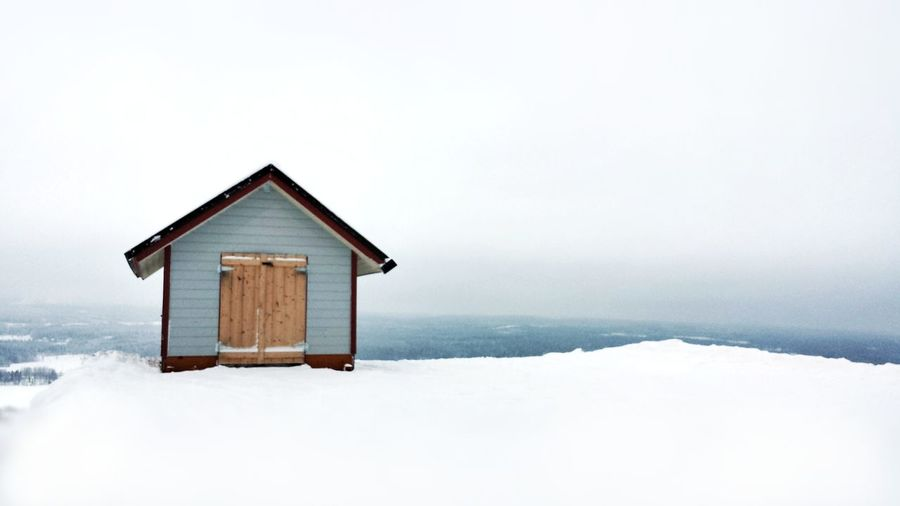 House on snow covered building against sky