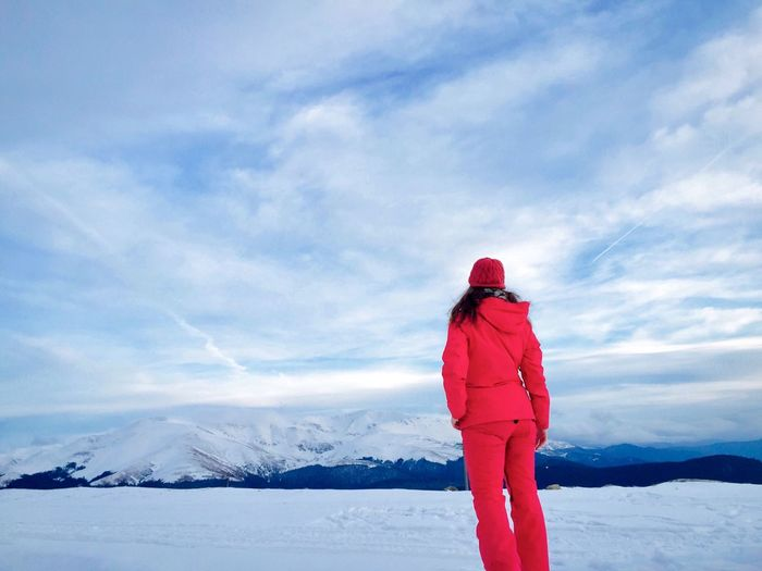 Back of woman hiker surrounded by snowcapped mountains Idyllic Landscape Snowcapped Mountain Travel Alone Hiking Hiker Outdoors Nature Day Woman Winter Snow Cold Temperature One Person Warm Clothing Red Sky Rear View Standing Full Length Snowcapped Mountain Mountain Beauty In Nature Real People Lifestyles Leisure Activity Scenics - Nature Clothing Cloud - Sky
