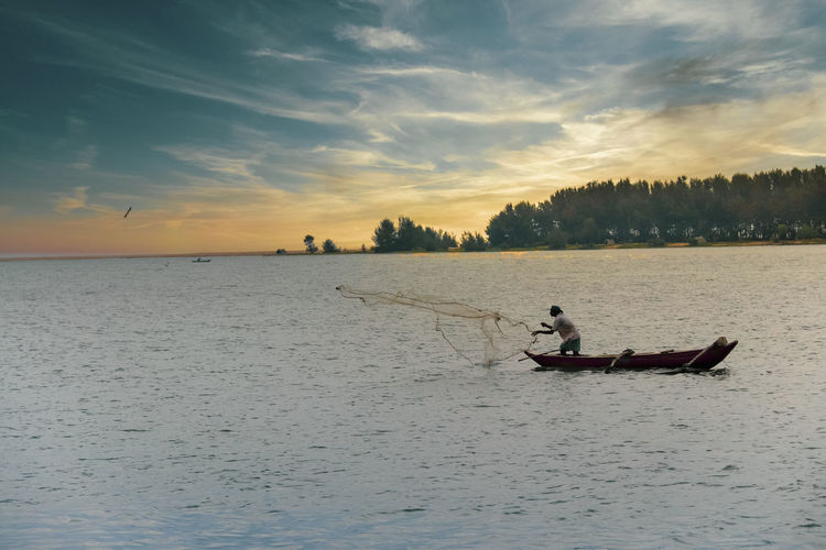 Man fishing in sea while standing on boat at sunset