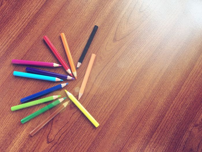 High Angle View Of Colorful Pencils On Wooden Table