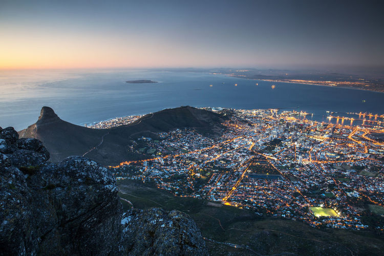 Aerial View Of Mountain And Illuminated City By Sea Against Sky At Dusk