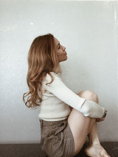 Side view of young woman sitting against wall