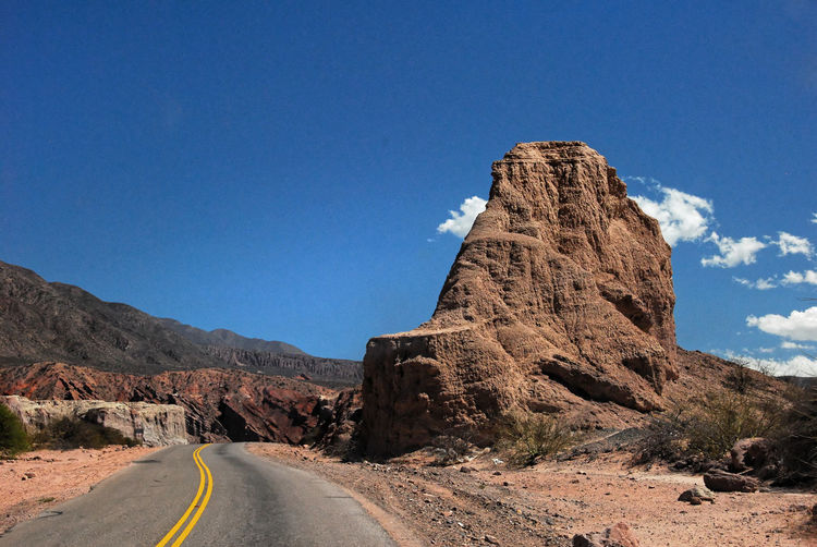 Rock formations by road against blue sky