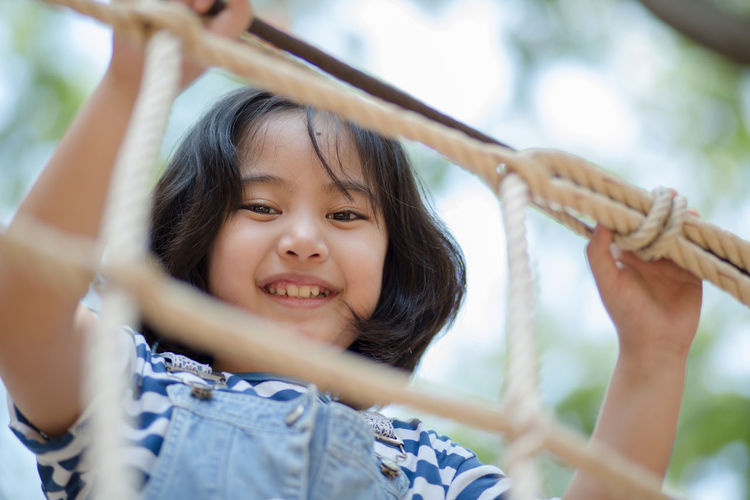 Happy Asian girl playing in playground Arms Raised Child Childhood Cute Day Emotion Females Front View Girls Hand Headshot Holding Human Arm Innocence Leisure Activity Lifestyles Outdoors Portrait Real People Selective Focus Smiling Two People Women