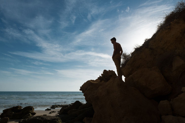 Silhouette man standing on rock formation at beach against sky
