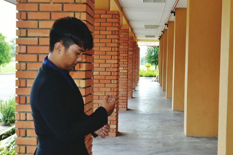 Side view of man standing in corridor