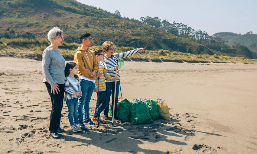 Grandmother pointing away to family at beach